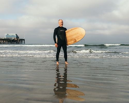 Russell Magnum with his surf board at the beach