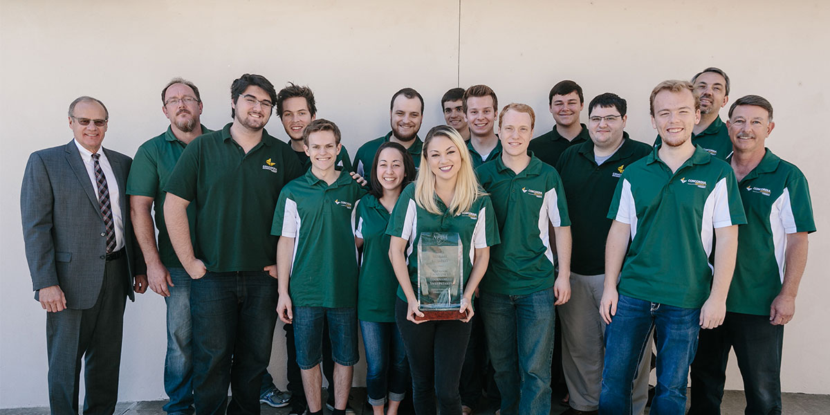 Debate Team standing with trophy