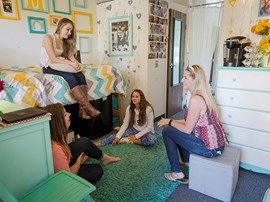 Four students in a dorm room talking.