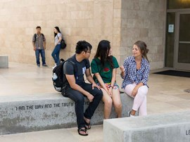 Students sitting and talking on stone bench.