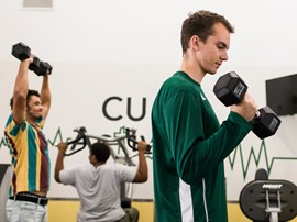 Students working out in CU Active fitness center.