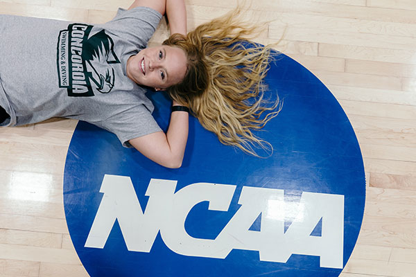 Bailee laying next to the new NCAA logo on the gym floor