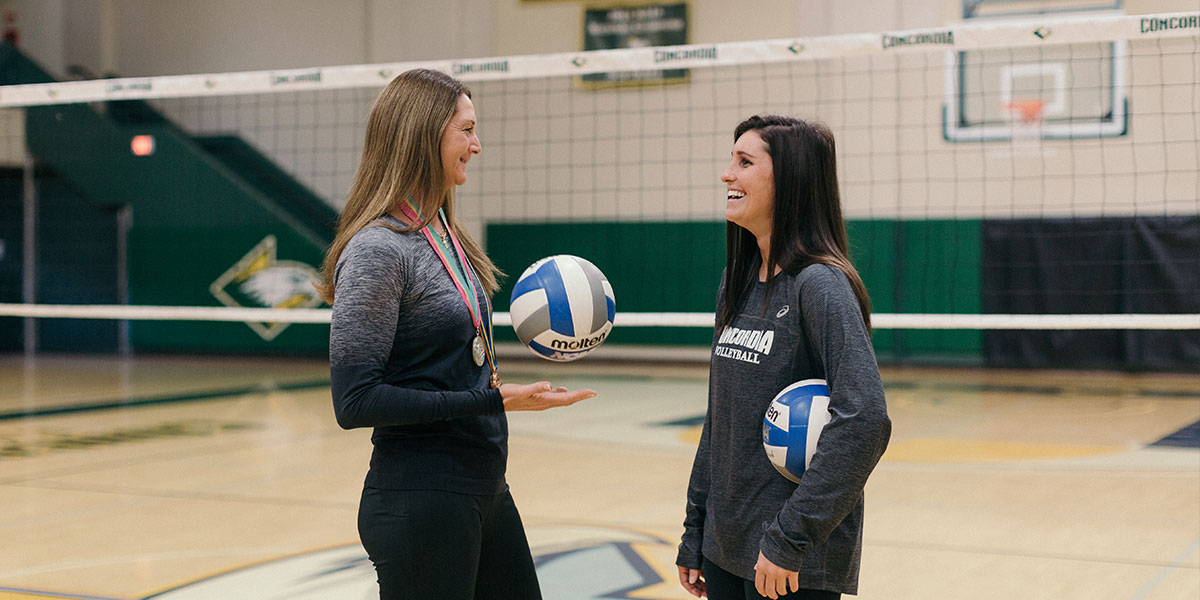 Volleyball coach and student-athlete in the gym