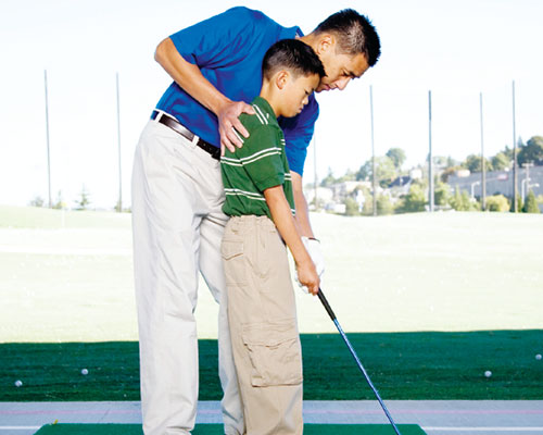 Father teaching his son to golf.