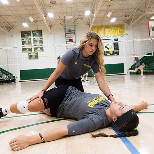 Athletic training student stretching an athlete.