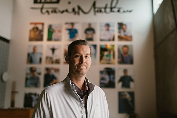 Ryan standing in front of Travis Mathew Team wall
