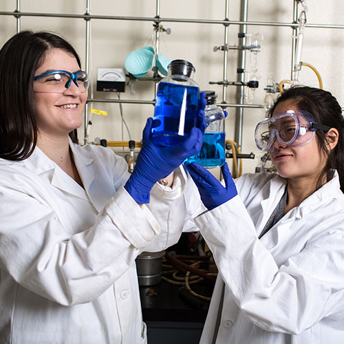 Two students inspecting beaker