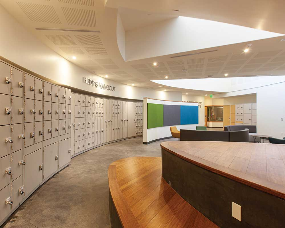 Instrument lockers flank the open student lounge in Hedy's Hangout, which has easy access to the Caryn Borland '85 Recording Suite., the bottom floor music lesson and practice room hallway, the music classroom, the music library, and the music office.