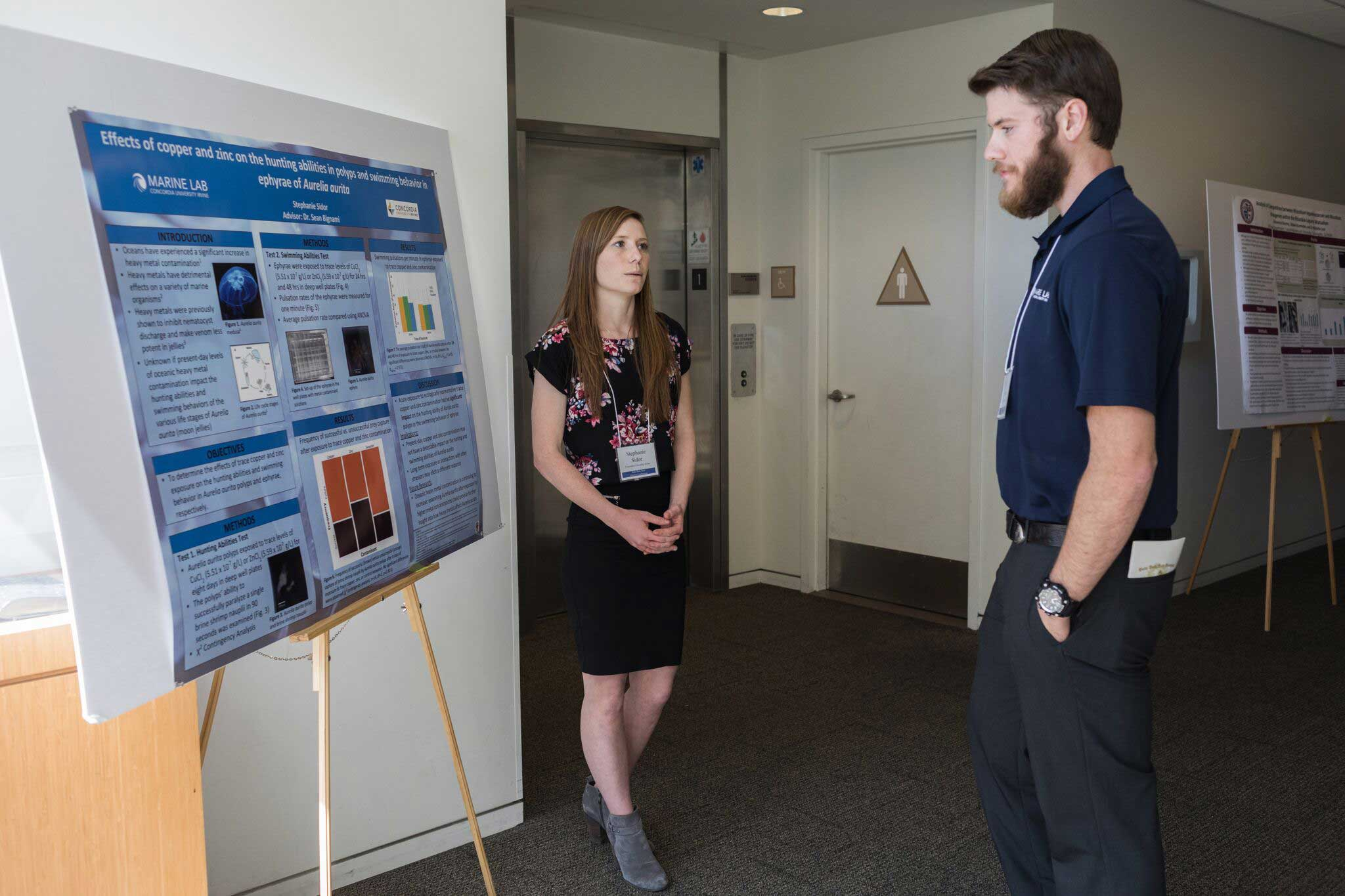 Noah Kolander viewing a female student's Marine Lab research poster