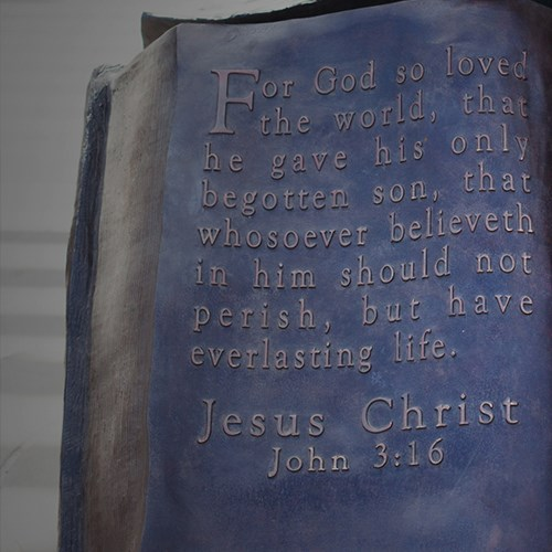 Bible sculpture of metal with a bible verse on it.