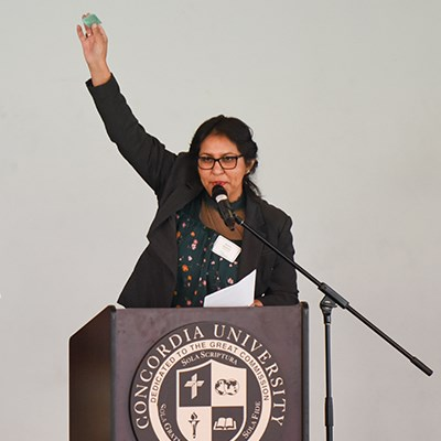 Young female conference speaker at podium with hand raised