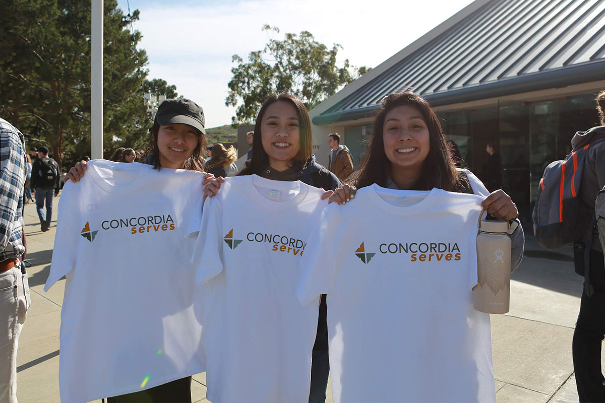 Three students showing their Concordia serves shirts
