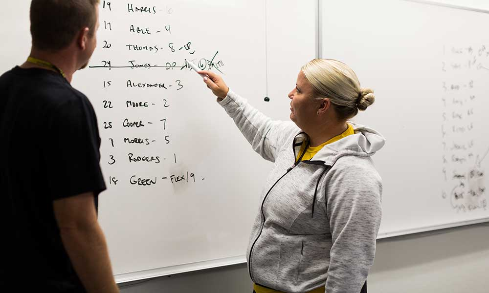 Softball writing a lineup on the whiteboard