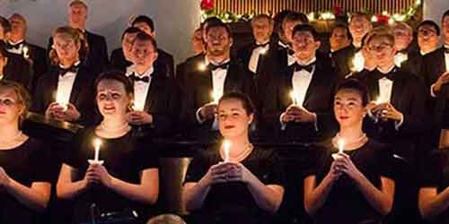 A choir in formal dress holds candles and sings