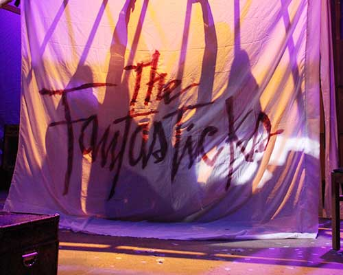 The Fantasticks opening scene of a sheet with silhouette shadows through a sheet