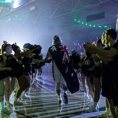Athletes enter the gym surrounded by cheer leaders and team members