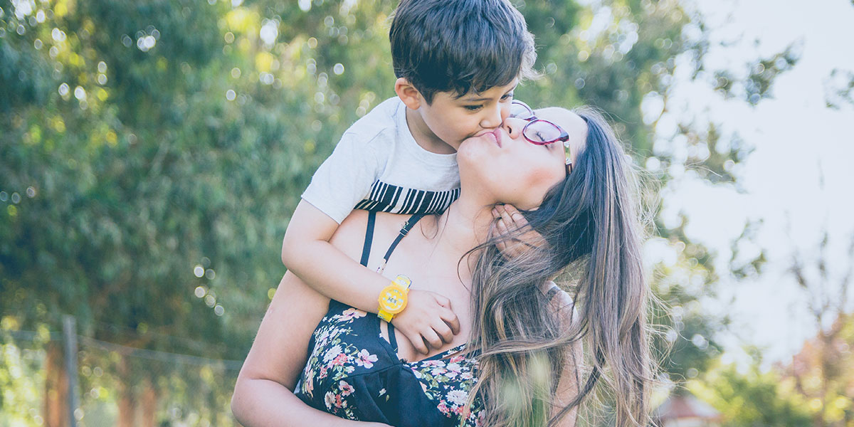 Young boy kisses mother