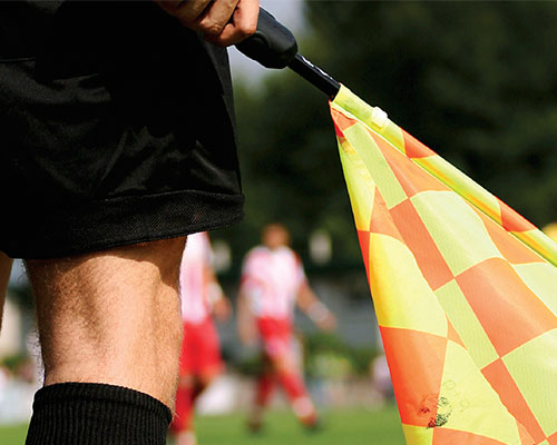 Referee holding a flag.