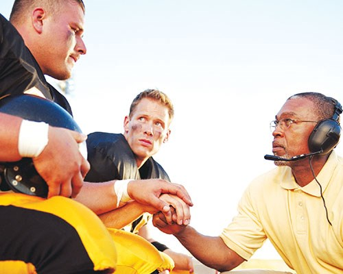 Coach talking to football player during a game.