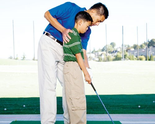 Father teaching his son how to golf.