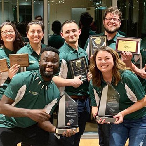 Members of the CUI Debate team hold plaques and award trophies they won at the National Parliamentary Debate Association Championship Tournament in March 2019.