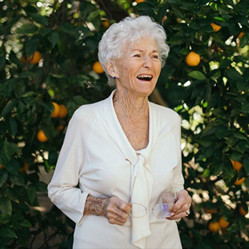 Elayne Lohr in front of multiple orange trees