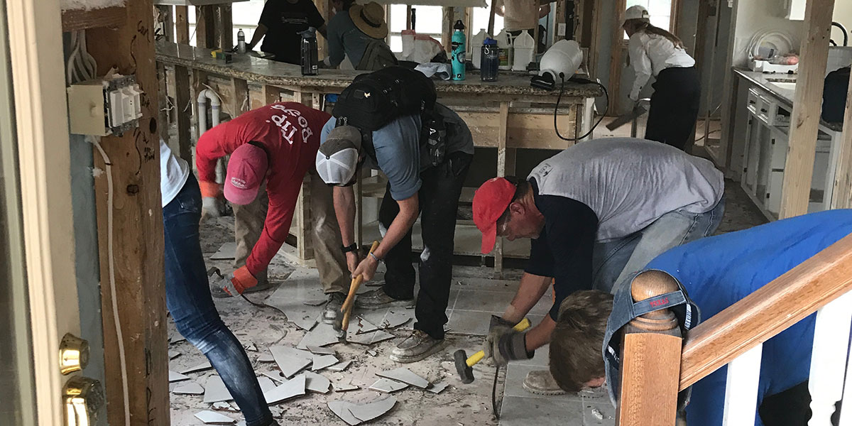 A team of people working together to fix a damaged home