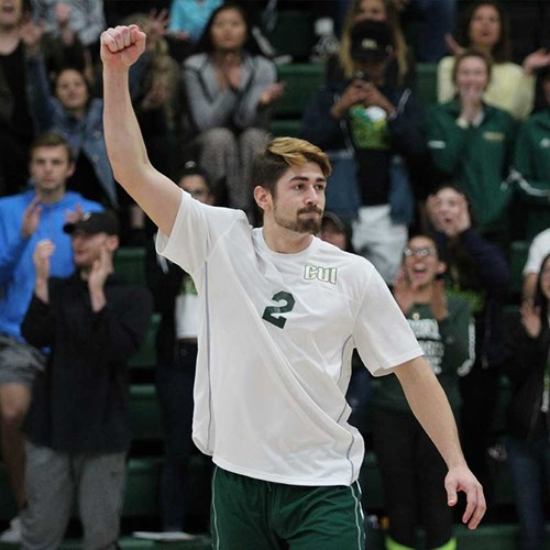 CUI men's volleyball player, Troy Makalena, raising fist in the air in celebration