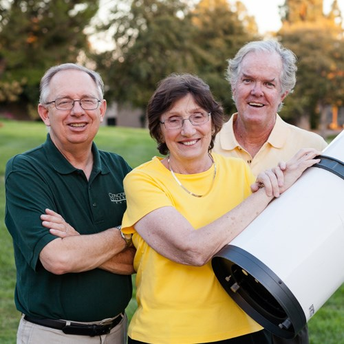 Faculty members pose in front of a telescope