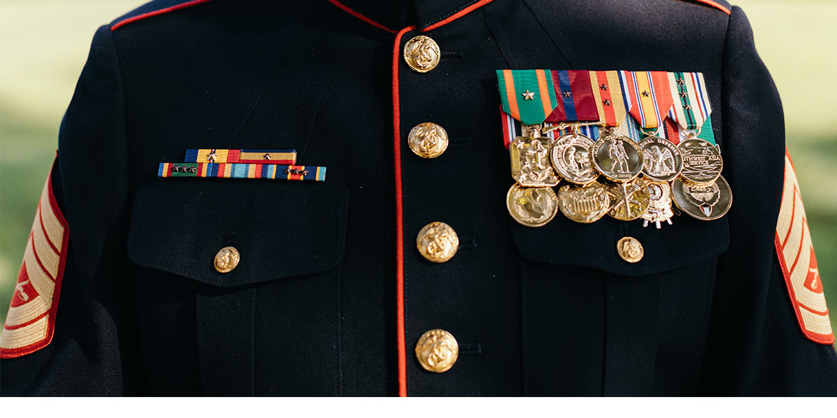 Shining metals fill John Gallegos chest on his Marine Corps Uniform.