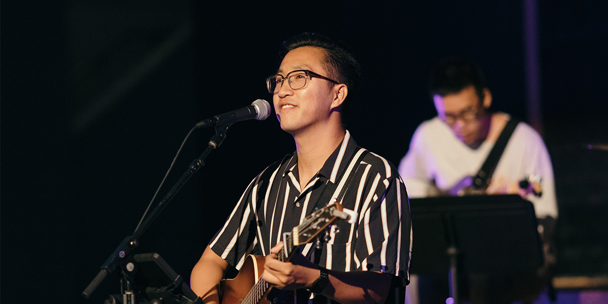 Brandon Li leads the crowd in worship while playing his guitar.
