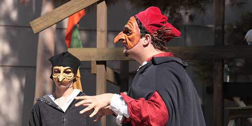 Two actors in exaggerated face marks and red hats talk on stage